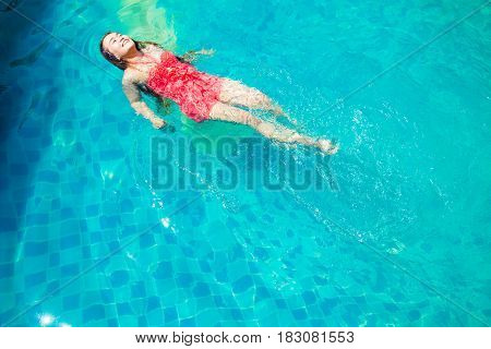 Asia Women swim in the pool in the morning of summer.