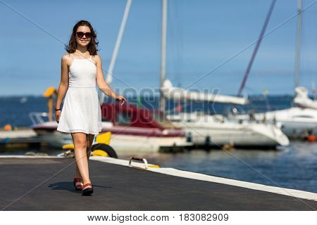 Young woman on vacation walking in harbor