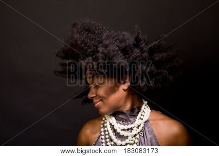 African American woman laughing and dancing isolated on black.