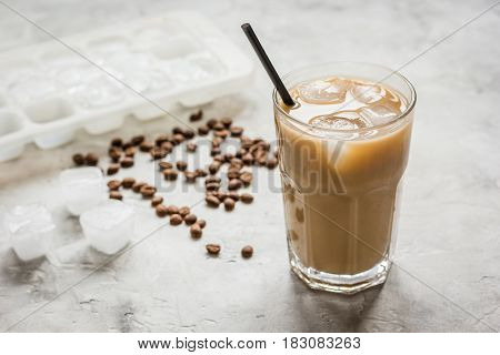 coffee break with cold iced latte and beans in caffee on stone table background