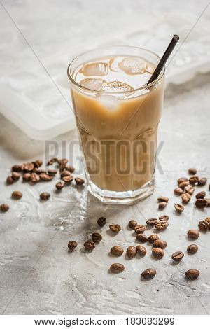 iced coffee with beans for cold summer drink on stone table background