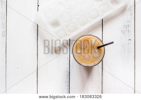 coffee break with cold iced latte and beans in caffee on white table background top view