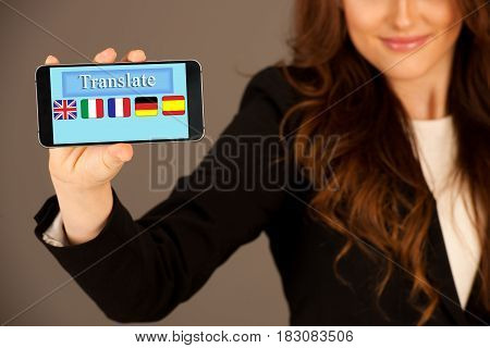attractive business woman holds a tablet or smartphone wtih with translate aplication on display