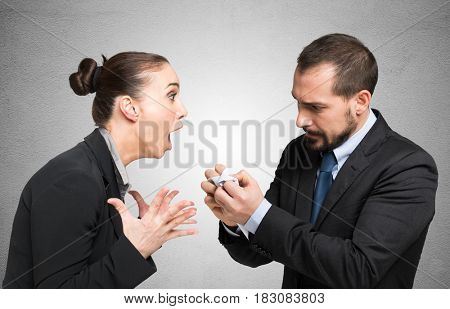 Woman yelling to a man crumpling a document