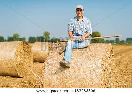 Smiling farmer relaxing on the hay in his field