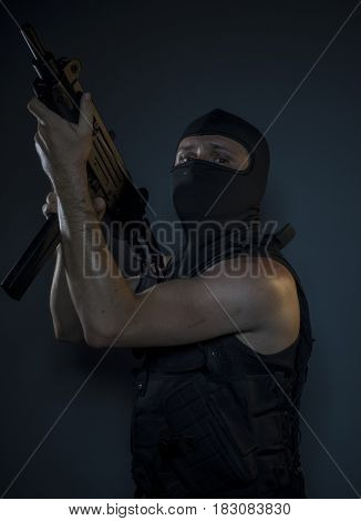 Military, Terrorist, a man dressed in a bulletproof vest and balaclava, is armed with pistols and machine guns