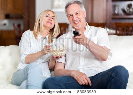 Portrait of a mature couple watching television