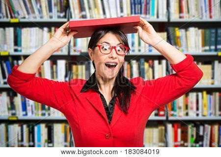 Smiling red dressed woman in a library