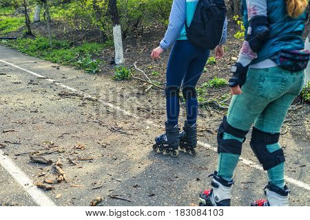 Two girls ride on rollers on a very bad road. The fallen branches lie on the asphalt. Sport Difficulties. Extreme rollerskating.