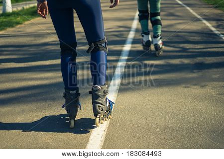 Two girls on roller skates ride along the road. Sport girls. One girl is ahead of the other. Second gitl is tired. View of legs.