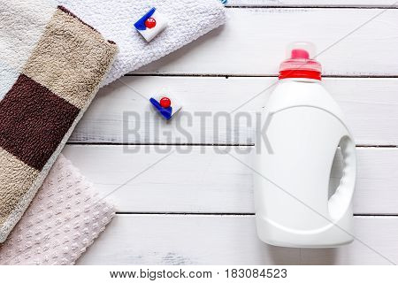 Bath towels stack with detergent plastic bottle in laundry on light table background top view