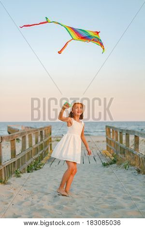 Girl play with rainbow colorful kite on the beach at sunset