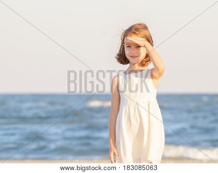 Little girl looking away with hand over the eyes at sunset
