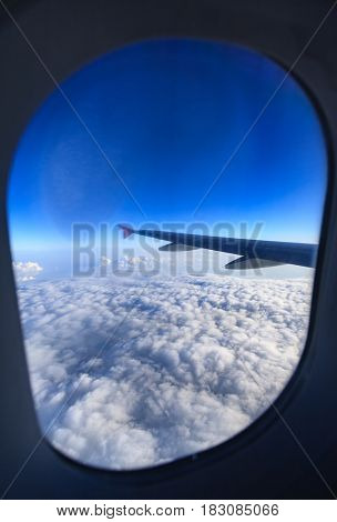Airplane interior view window with wing flying above the clouds at sunset