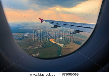 Airplane interior view window with wing flying above the river at sunset