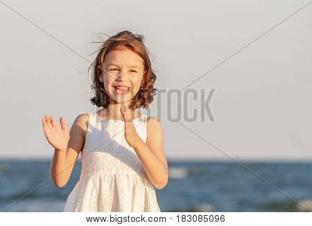 Kid girl applause and laughing on the beach at sunset