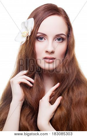 Beautiful young woman with pale skin and natural long red brown hair with orchid flower in it. Isolated on white background. Copy space.