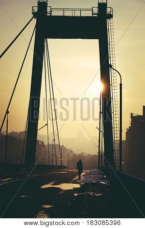 Photo in summer blockbuster look of City landscape with a lonely man walking through an empty bridge.