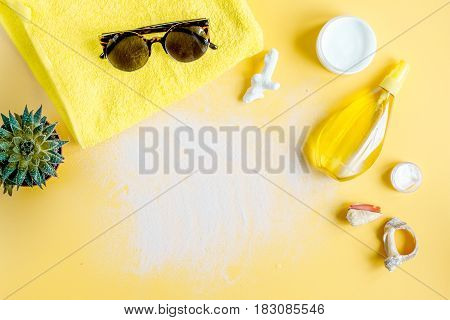 Sun protection concept with cream and lotion and summer accessories, sunglasses on orange background top view mockup