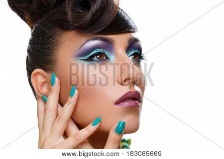 Beautiful young woman with bright purple make-up and fancy hairdo. Long green nails. Beauty shot isolated on white background. Copy space.