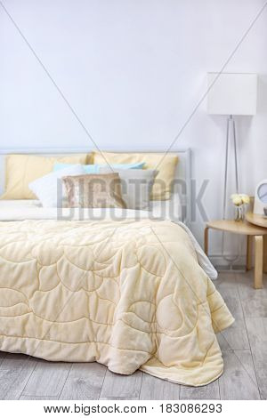 Comfortable bed with coverlet in light bedroom interior