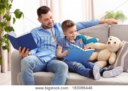 Dad and son reading interesting books at home