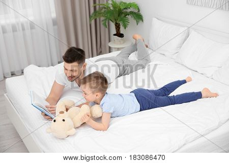 Dad and son reading interesting book while lying on bed at home