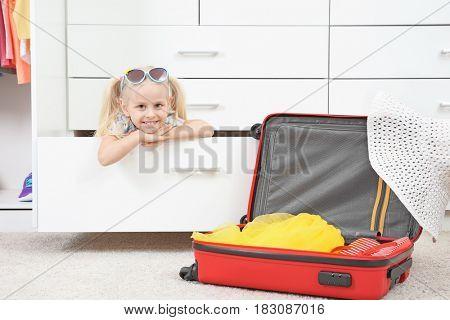 Cute small girl playing in wardrobe