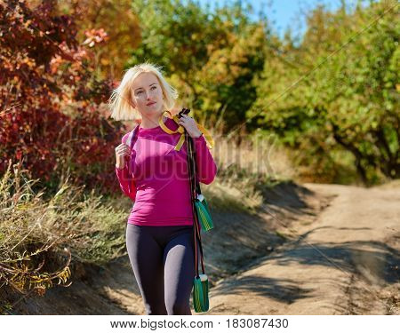 Young smiling woman with suspension straps going to training in park
