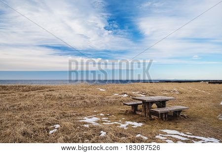Wooden seat with table in empty field with blue sky