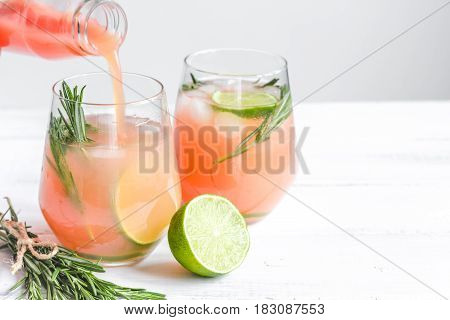 vegetable smoothie with lime pieces and fresh rosemary in glass on white table background mock up