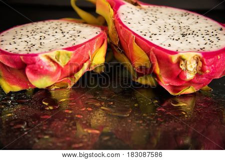Fresh dragon fruit cut in half on a black reflective background with drops of water