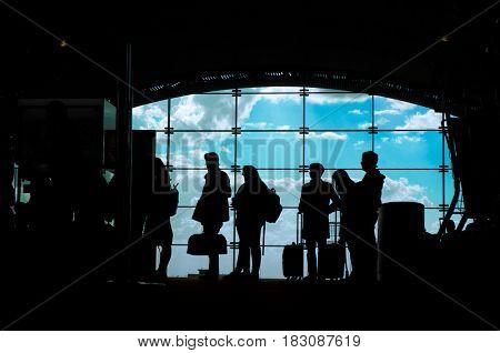 Silhouettes of people waiting for their flight at the airport.