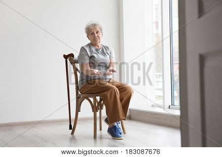 Senior woman counting coins while sitting on chair in empty room. Poverty concept