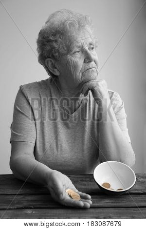 Senior woman sitting at table with bowl and coins. Poverty concept