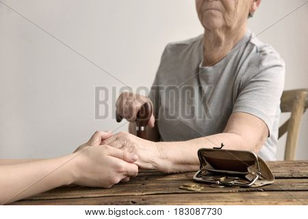 Young woman holding hand of elderly one sitting at table with purse and coins. Poverty concept