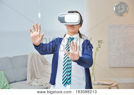 Schoolgirl with virtual reality glasses at home