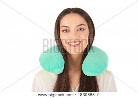 Beautiful young woman with travel pillow on white background