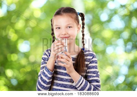 Little girl with glass of clean water on blurred background