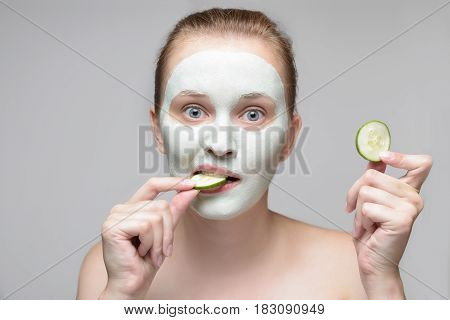Girl with green cream on face. Beautiful young woman with homemade mask biting a cucumber