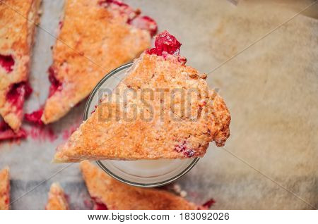 Freshly baked strawberry scone segments with pieces of berries on aglass of milk. Close up and Top view.