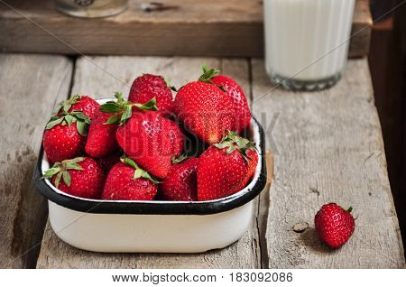 Heap of fresh ripe raw strawberries in a bowl and glass of milk on a wooden background. Rustic style and close up.