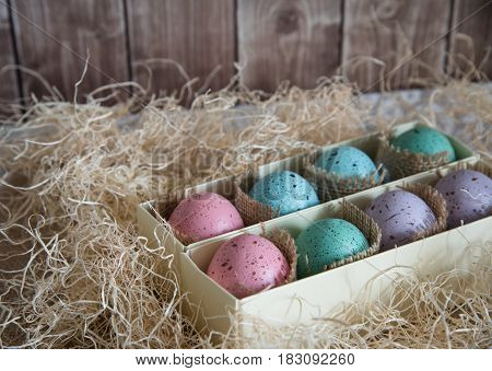 assorted colorful painted easter eggs in a gift box on wooden background with woodchips