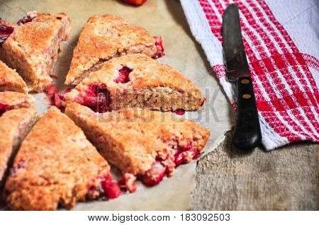 Freshly baked strawberry scone segments with pieces of berries on a parchment paper. Close up and rustic style.