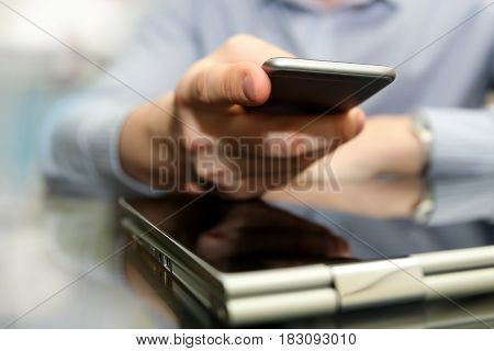 Business man working and analyzing financial figures on a graphs using laptop and mobile phone