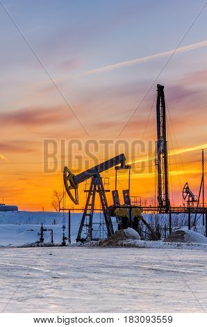 Pump jack, wellhead and oil rig during sunset in the oilfield. Winter period. Oil and gas concept.
