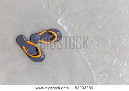 Brown and orange beach slippers soak with waving ocean summer vacation concept.