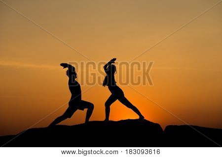 Silhouette of attractive confident half naked man and woman doing yoga on beach rock for wellness yoga zen meditation fitness mind body training healthy happy relax smile wonderful sun set beach