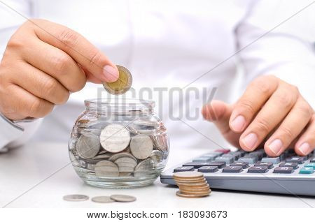 Male hand putting money coins into glass jar bank for saving money concept