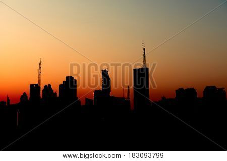 silhouette of urban city sunset with tall sky scrapers telephone towers financial building for sunset resting money business happy new dawn era Bangkok city concept design